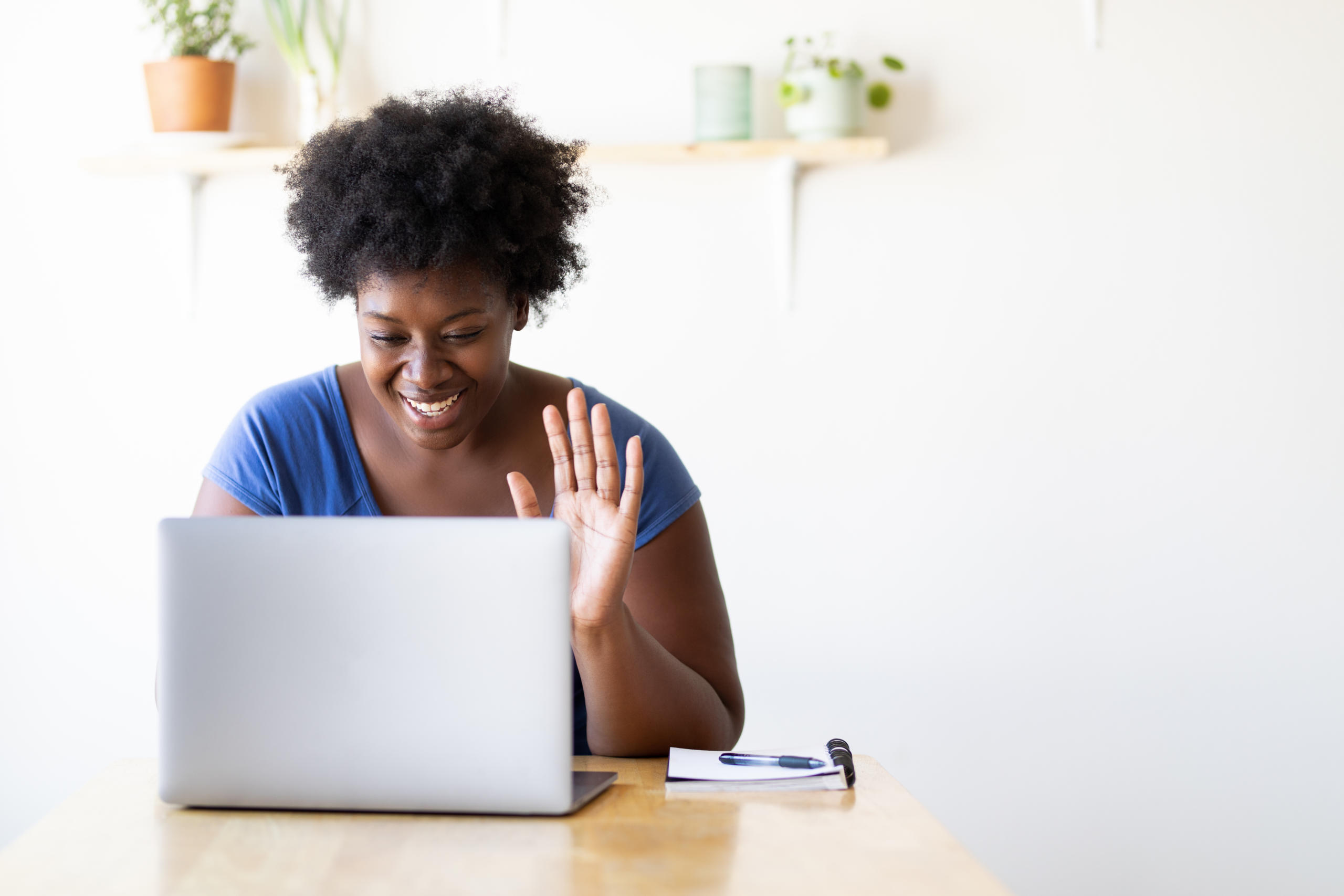 Woman at home having a virtual video call on her laptop.