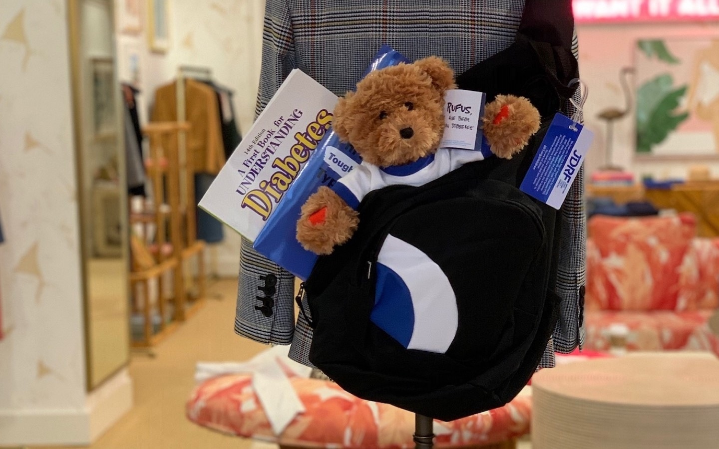 Photo of Rufus The Bear with Diabetes and other Bag of Hope items in a bookbag hanging in a Veronica Beard store.